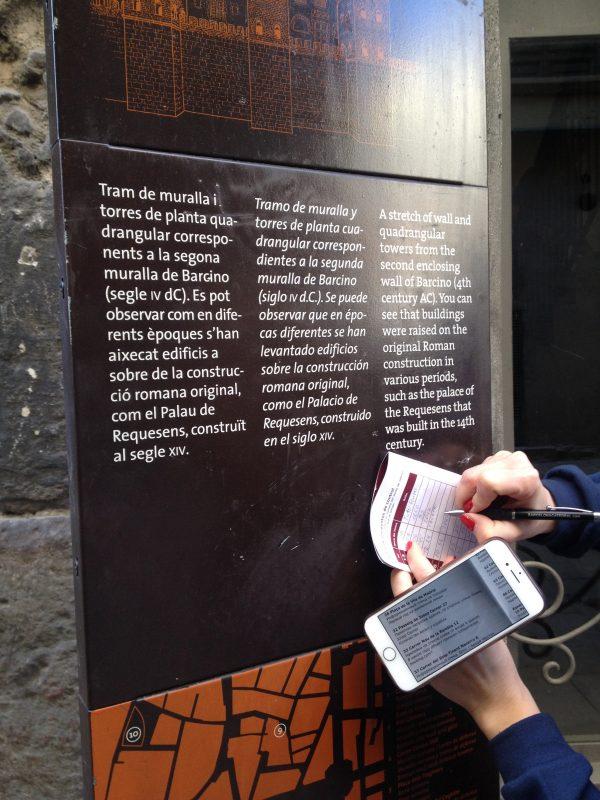 Участники ищут информацию на табличке в Барселоне